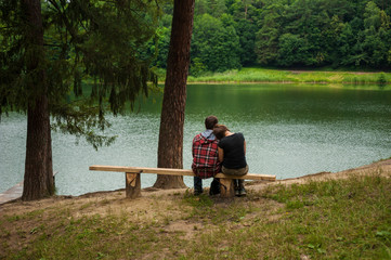 Couple sitting on a bench and looking at the lake