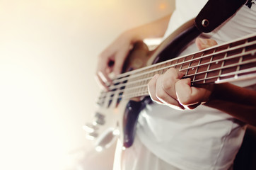 Unrecognizable man playing five string bass guitar. color image in horizontal orientation