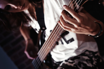 Young adult girl playing five string bass guitar. Color image