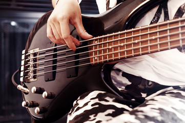 Young adult girl playing five string bass guitar. Color image in horizontal orientation