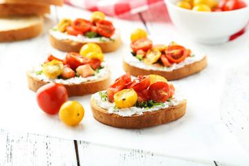 Tasty fresh bruschetta with tomatoes on white wooden background