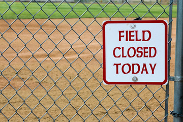 Looking through a chain link fence at the infield of a softball field with a field closed today sign posted