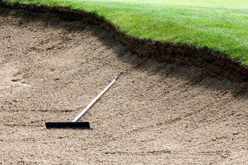 Rake in the middle of a deep sand bunker on a golf course