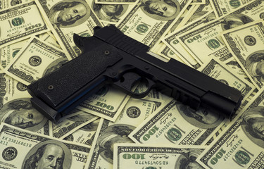 Black and chrome gun pistol and money dollars background filtered