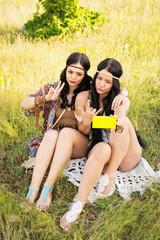 Two beautiful boho young women taking a selfie in summer