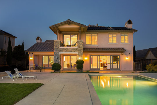Luxurious and modern house with deckchairs, swimming pool at night.