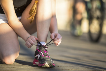 Girl is tying close-up the laces sports shoe before running. Running, healthy lifestyle.