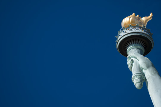 Statue of Liberty close-up torch against bright blue American sky