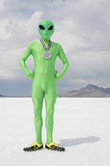 Green alien athlete wearing gold medal standing on stark white planet background