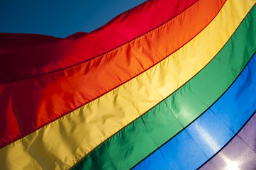 Gay pride rainbow flag fills the frame for a colorful background