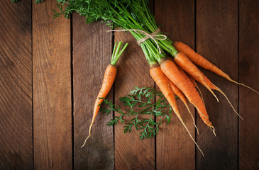 Bunch of fresh carrots with green leaves over wooden background.