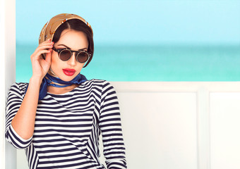 Beauty portrait of sexy smiling brunette woman with red plump lips and trendy sun glasses with colorful scarf on her head relaxing on the yacht. Cruise summer fashion. Ocean background with copy space