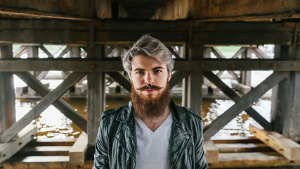 Bearded hipster with nose ring in leather jacket
