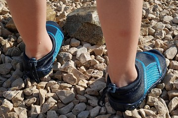 5 years old boy feet with aquatic blue shoes on rocky beach