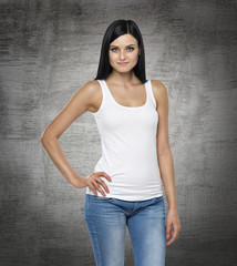 Close up of the brunette lady in a white tank top and denims. Concrete background