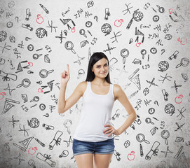 Brunette lady is presents a necessity of higher education. Educational icons are drawn over the concrete background.