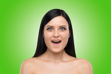 Portrait of an astonished brunette girl. Green background.