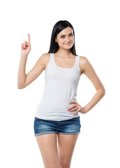 Close up of a brunette lady in a tank top and denims who points her finger up. A concept of a new idea. Isolated.