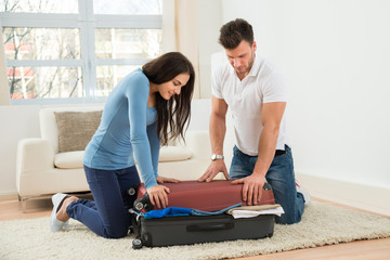 Couple Trying To Close Suitcase With To Much Clothes