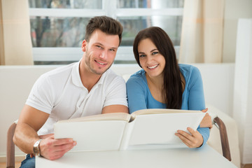 Happy Couple Holding Photo Album