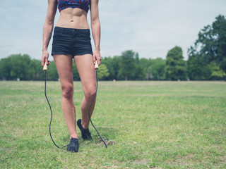 Fit woman in park with jump rope