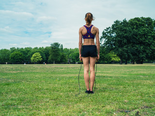 Woman in park exercising with jump rope