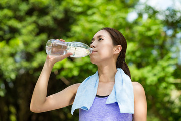 Young woman having rest after sport exercises holding bottle of