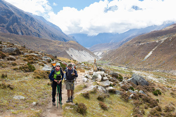 Wall Mural - Couple backpackers hiking mountain trail in Nepal.