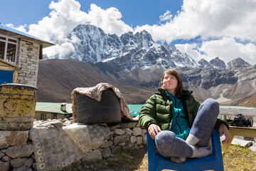 Wall Mural - Young woman tourist sitting resting mountains ridge view.
