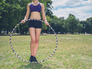 Fit woman in park with hula hoop