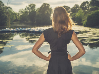 Young woman standing by lake at sunset