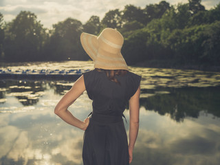 Elegant woman with hat by lake