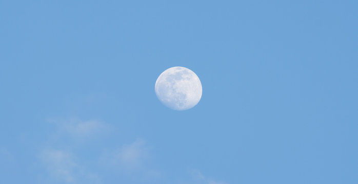 The full moon in the sky during the day.