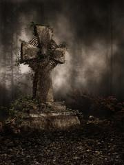 Nagrobek z krzyżem pokryty jesiennym bluszczem w ciemnym lesie