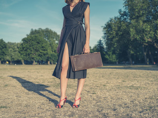 Young woman with briefcase in park