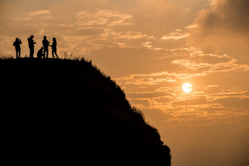 Friends standing on the top of mountain with beautiful sunrise.