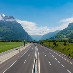 Empty highway is among the alpine mountains and fields. Path of Switzerland towards Italy St. Gotthard tunnel.
