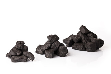 Three small piles of black coal on a white background