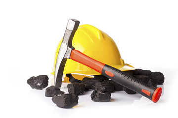 Yellow helmet with mining pickax and loose lumps of black coal on white glossy table