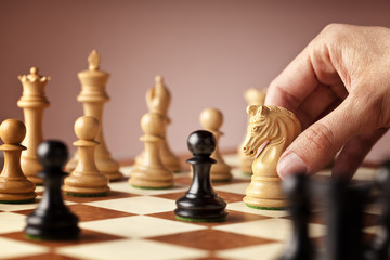 Male hand moving the white chess knight in the middle of a chess game attacking the blacks