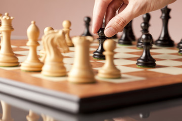 Male hand moving the black pawn in focus on the wooden chessboard in the middle of a chess game