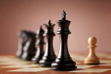 A line of luxurious chess pieces carved in genuine ebony wood facing a single white pawn made of natural boxwood standing on superior traditional wooden chessboard