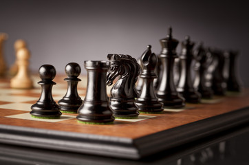 Left flank of the black army of luxurious chess pieces in focus on a wooden chessboard with dark background