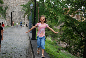 Little girl running and smiling in a park in Budapest, Hungary