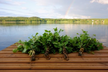 Traditional Finnish bath whisks made out of fresh birch leaves and twigs on a wet jetty by the lake on a Midsummer Eve.