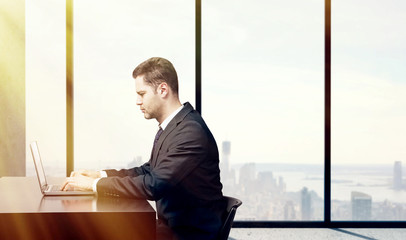 busienssman sitting in office with  laptop