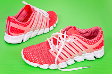 New orange and white running shoe, sneaker or trainer on green b