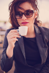 Young woman at cafe drinks coffee