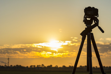 Silhouette from a recording camera on a tripod during sunrise