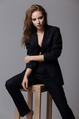 woman in black suit sits on a chair